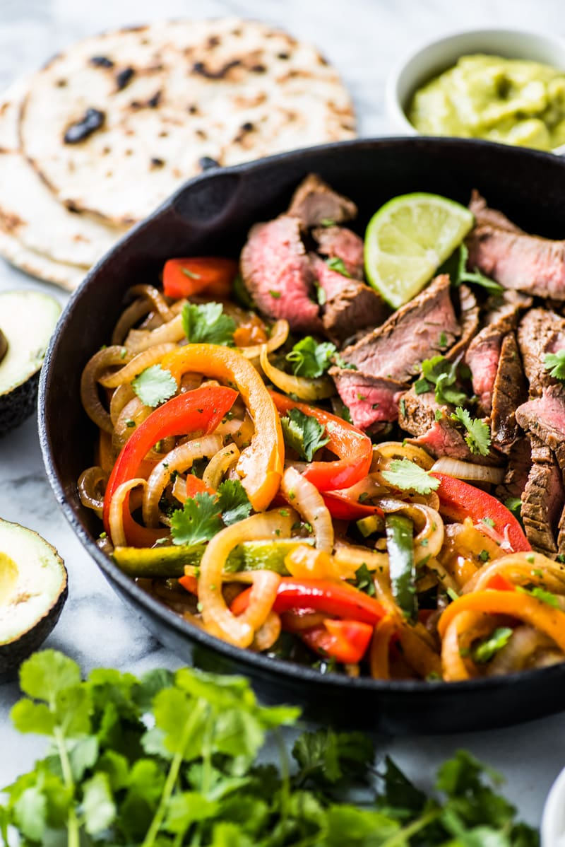 Peppers and onions in a black cast iron skillet with steak fajitas.