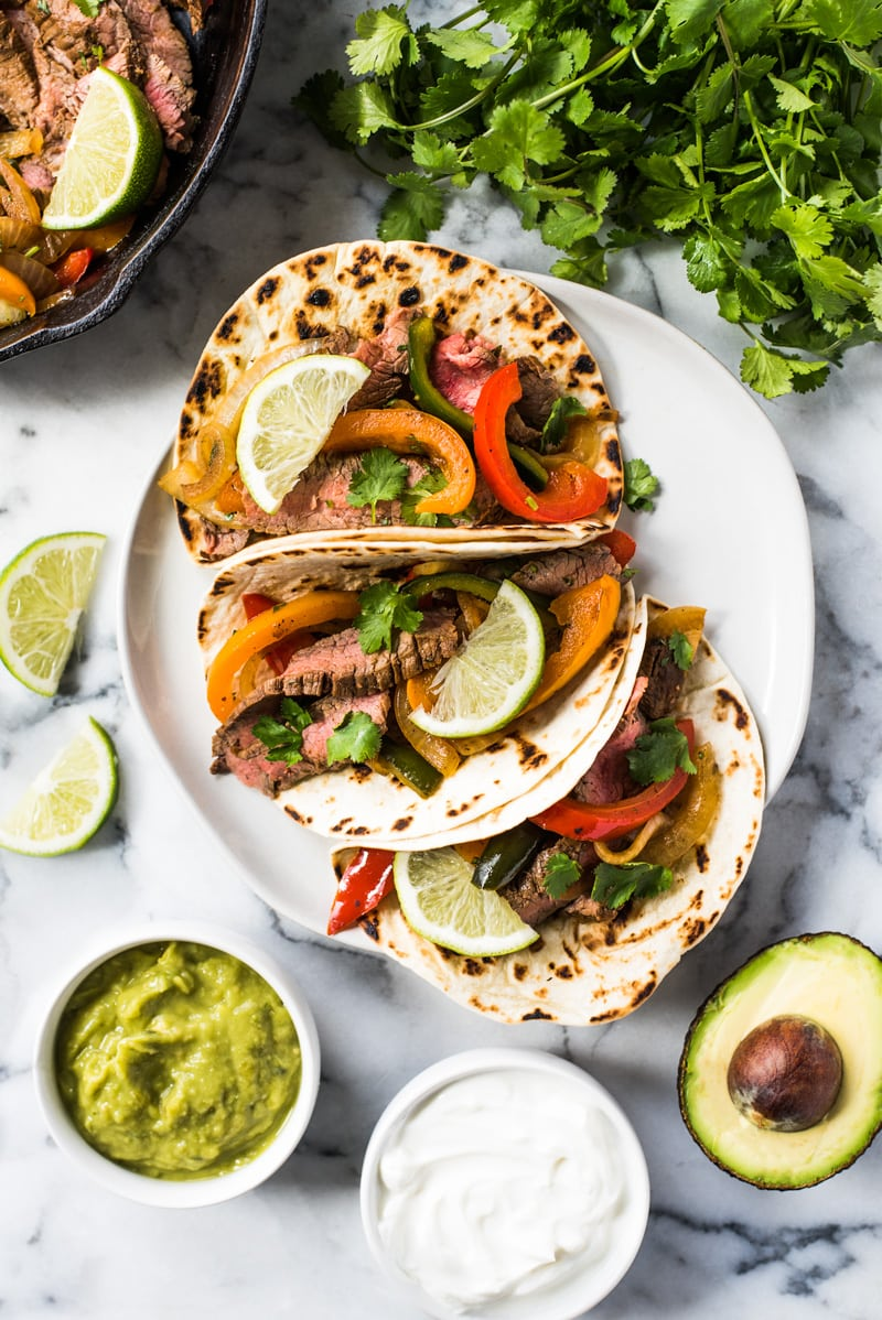 Sliced steak fajitas in warm flour tortillas with peppers and onions.