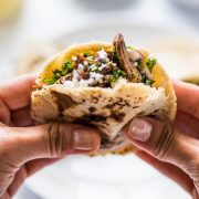 Two hands hold a gordita stuffed with meat and cheese.