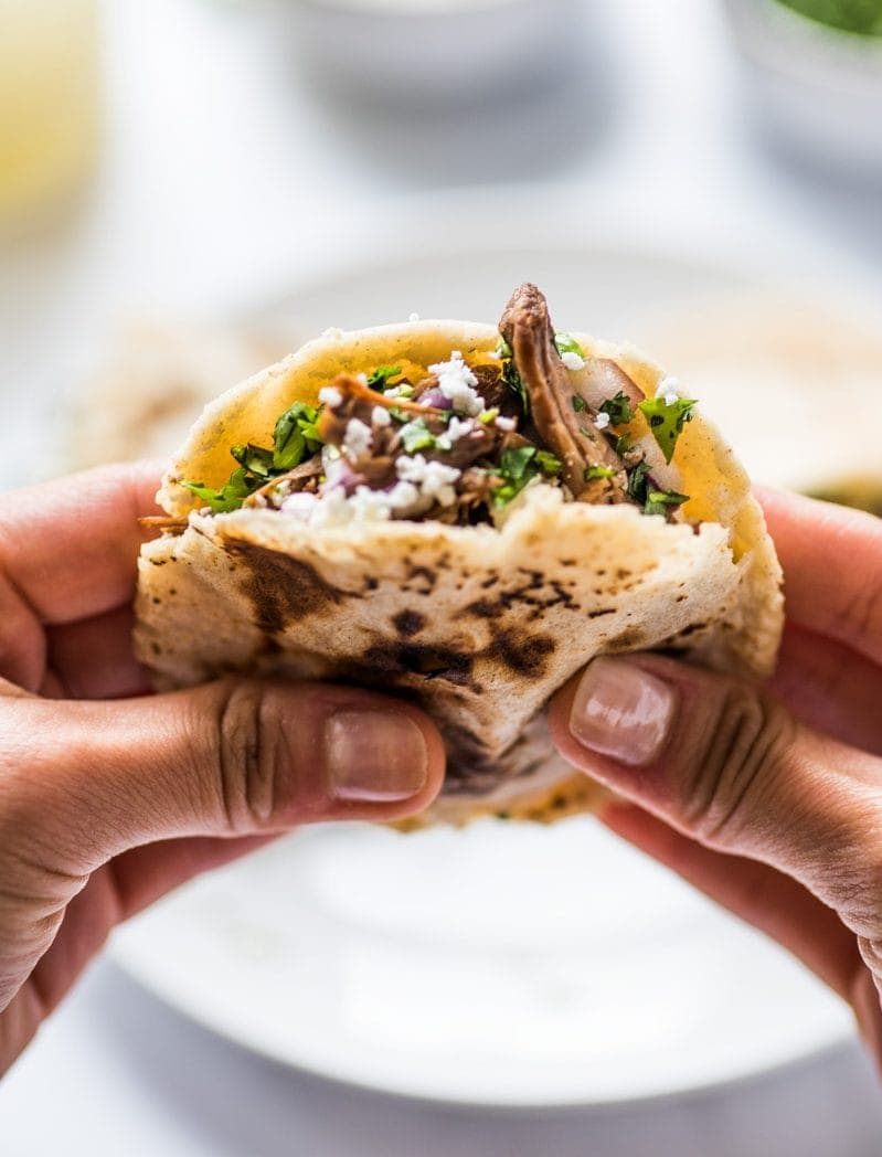 A hand holding a gordita stuffed with shredded beef, cheese and cilantro.