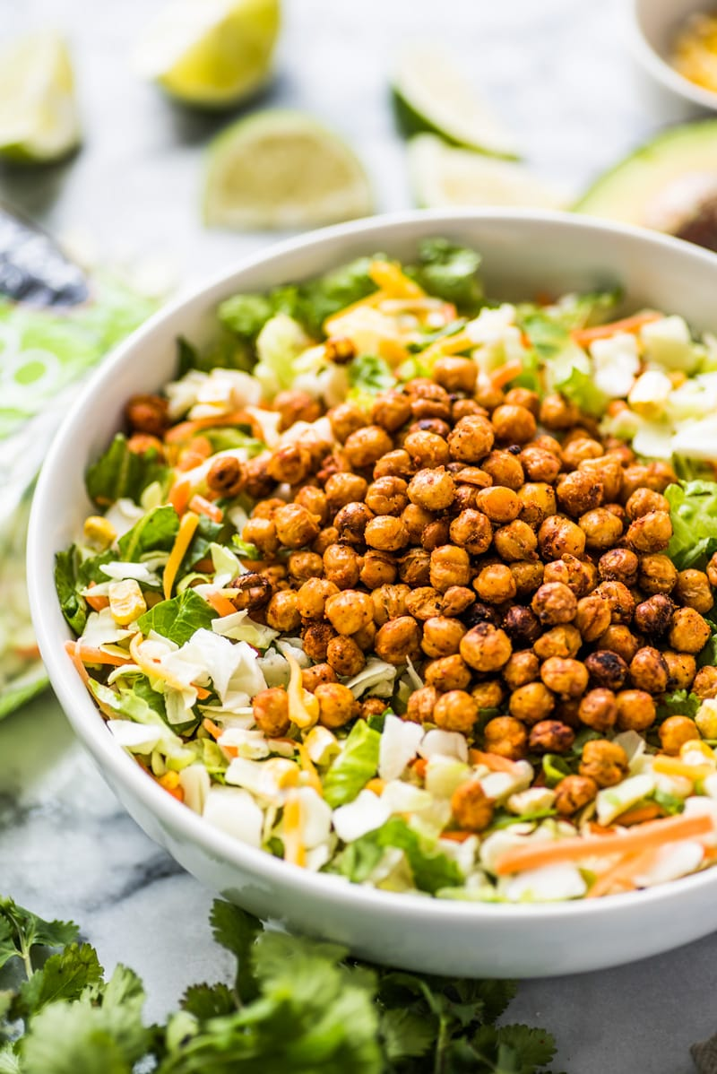 Chopped salad recipe topped with roasted chickpeas and avocado ranch dressing.