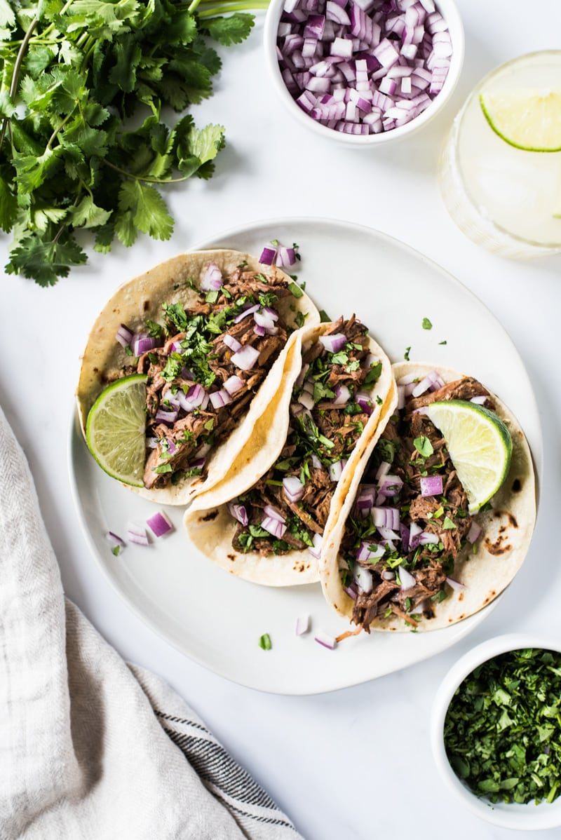 Barbacoa beef in tacos on a white plate.