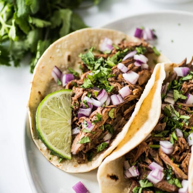 This Mexican Barbacoa Recipe is made in the slow cooker or Instant Pot for easy and flavorful shredded beef that can be served in tacos, salads, burritos and more! (gluten free, low carb, paleo)