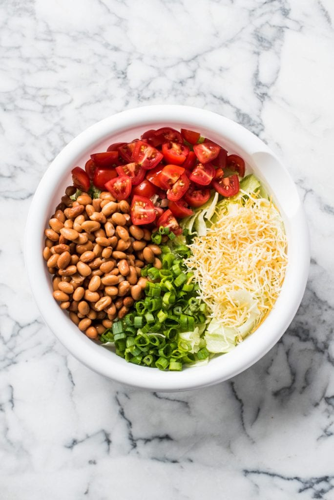 A white mixing bowl filled with chopped tomatoes, pinto beans, iceberg lettuce, cheese and green onions for taco salad.