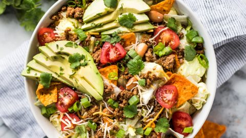 This Taco Salad recipe is the absolute best! Made with seasoned ground beef, chopped lettuce and all your favorite toppings (including nacho-flavored tortilla chips), this salad is ready in under 30 minutes and the kids will love it!