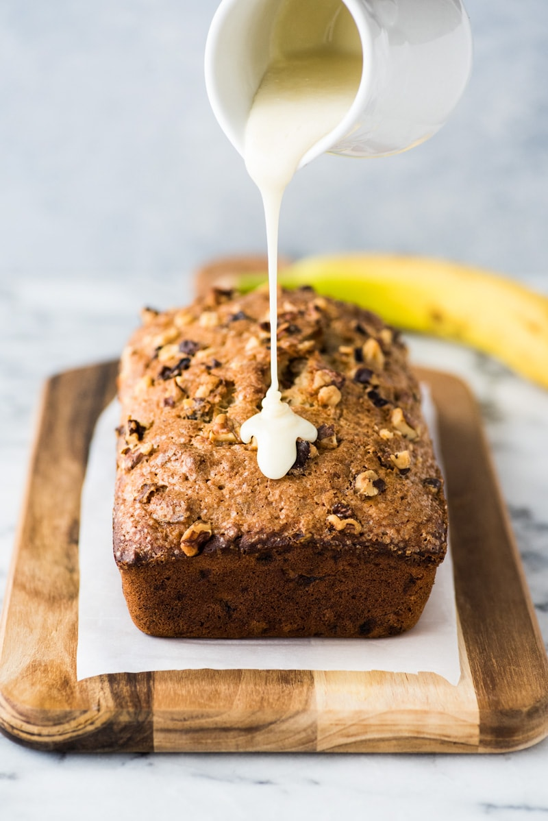 glaze being pour over banana bread