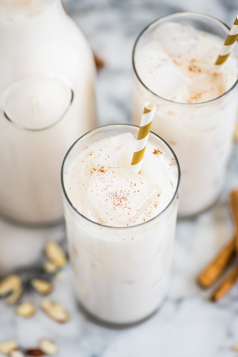 Horchata in a glass with ice cubes topped with cinnamon.