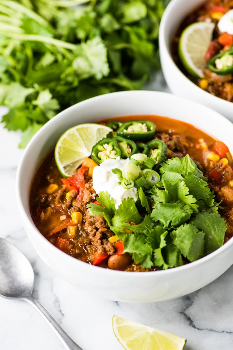 Taco soup topped with cilantro, sour cream and lime juice.