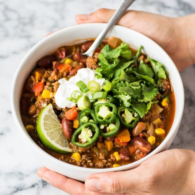 This taco soup recipe is hearty, healthy and ready in only 1 hour! An easy and healthy meal cooked up on the stovetop, serve it with your favorite taco toppings and tortilla chips for a little crunch! (gluten free, freezer friendly) #tacosoup #souprecipe #mexicanfood