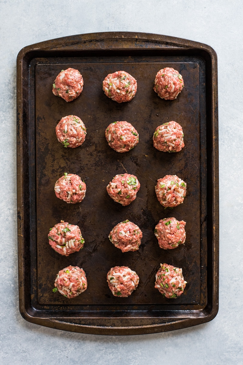 Albondiga meatballs on a weathered brown baking sheet.