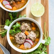Albondigas soup in a white bowl topped with fresh cilantro and sliced radishes.