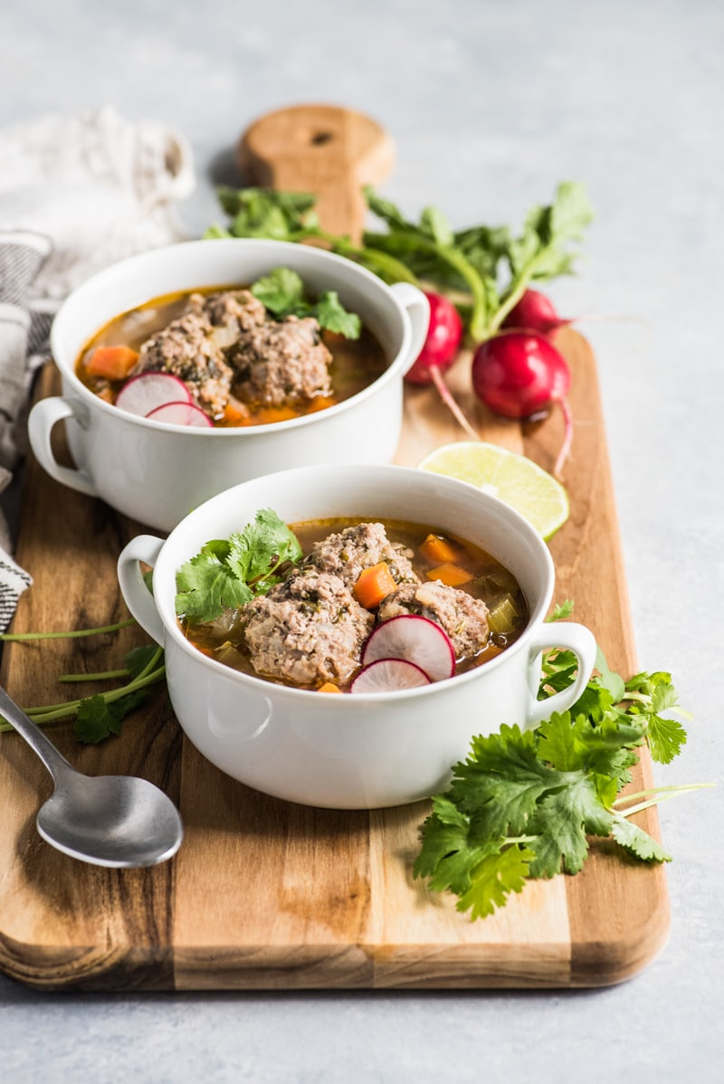 Albondigas soup in a white bowl with a spoon next to it.