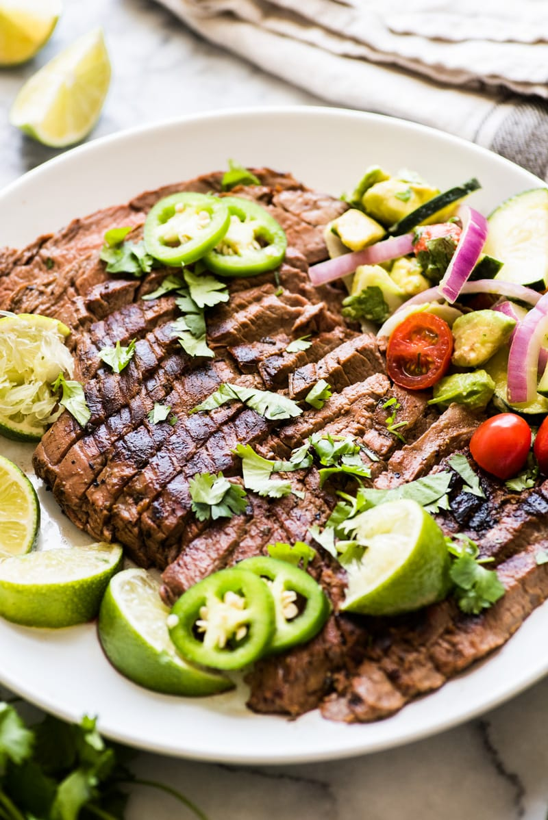 Grilled carne asada sliced against the grain and placed on a white plate.
