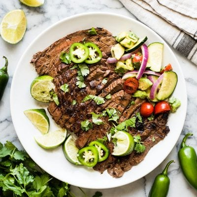 Thinly sliced carne asada on a white plate served with fresh lime wedges and jalapenos.