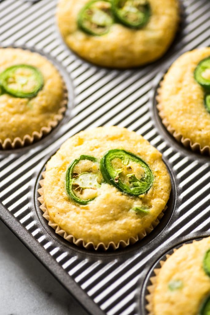 Jalapeno Cornbread muffins topped with sliced jalapenos in a muffin tin.