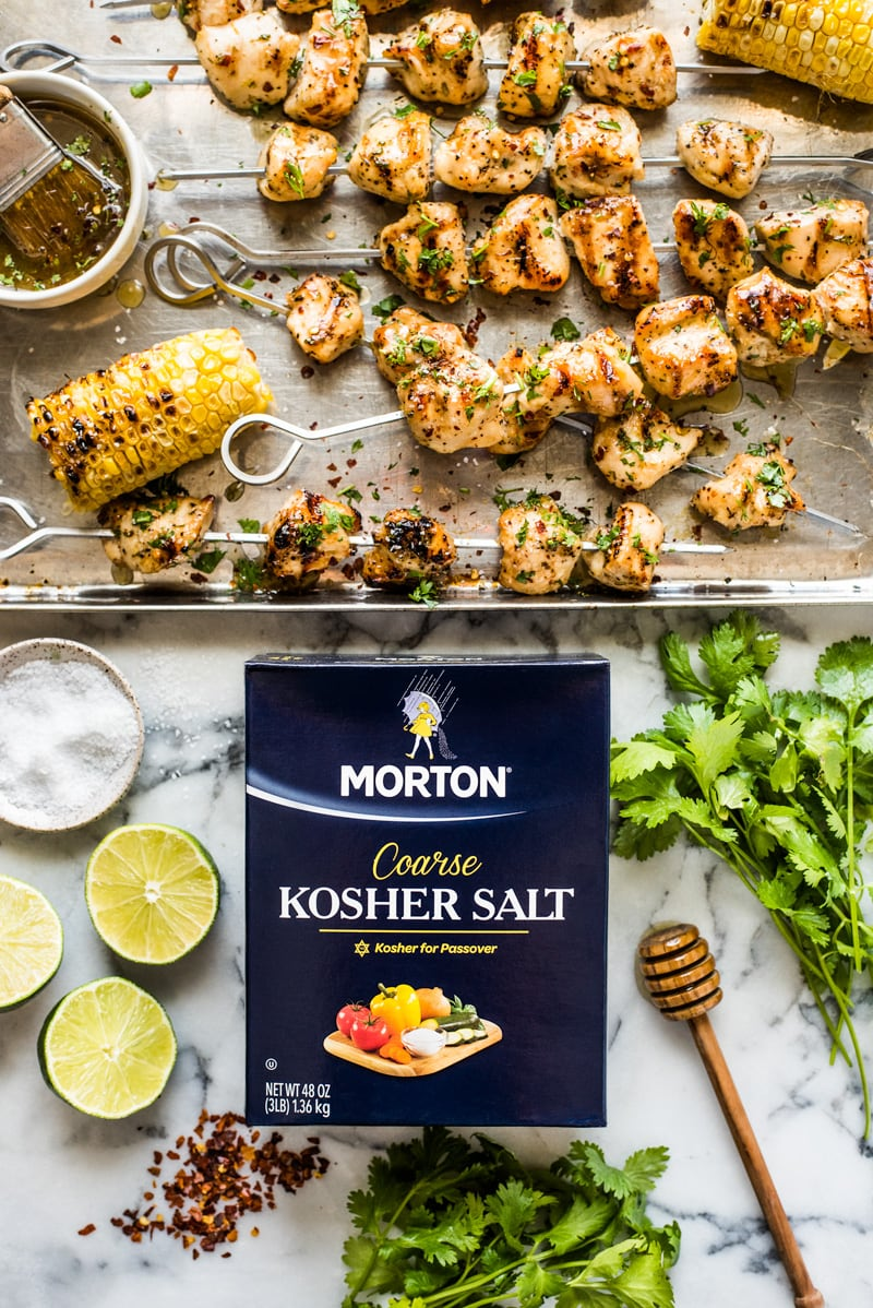 Chicken kabobs on a baking sheet next to Morton Coarse Kosher Salt, cilantro, limes and red pepper flakes.