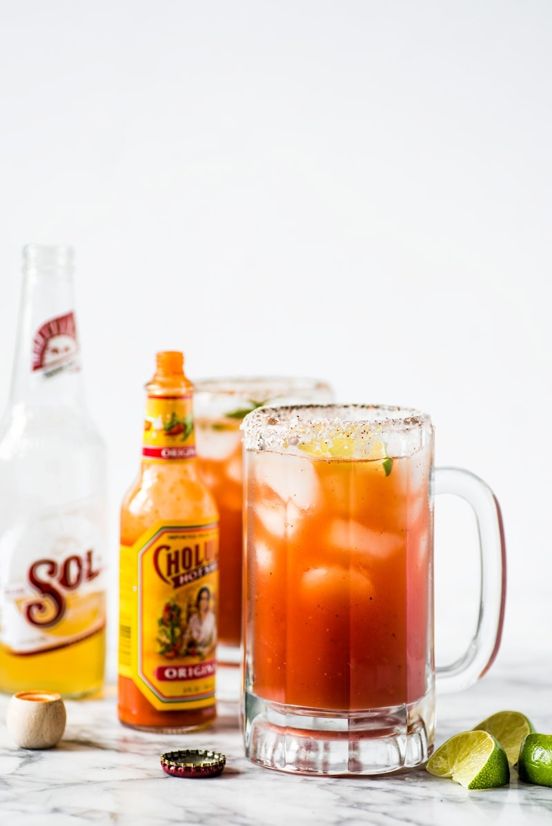 A Michelada in a glass rimmed with salt and chili powder.