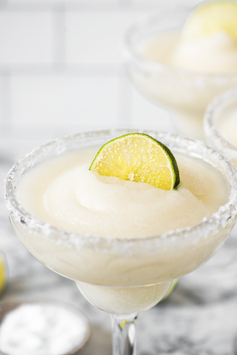A lime wedge on top of a frozen margarita.