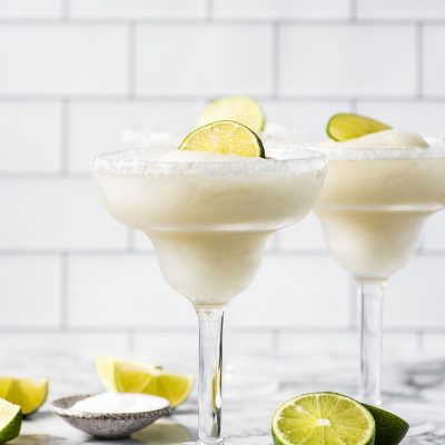 Frozen margaritas in glasses topped with lime wedges.