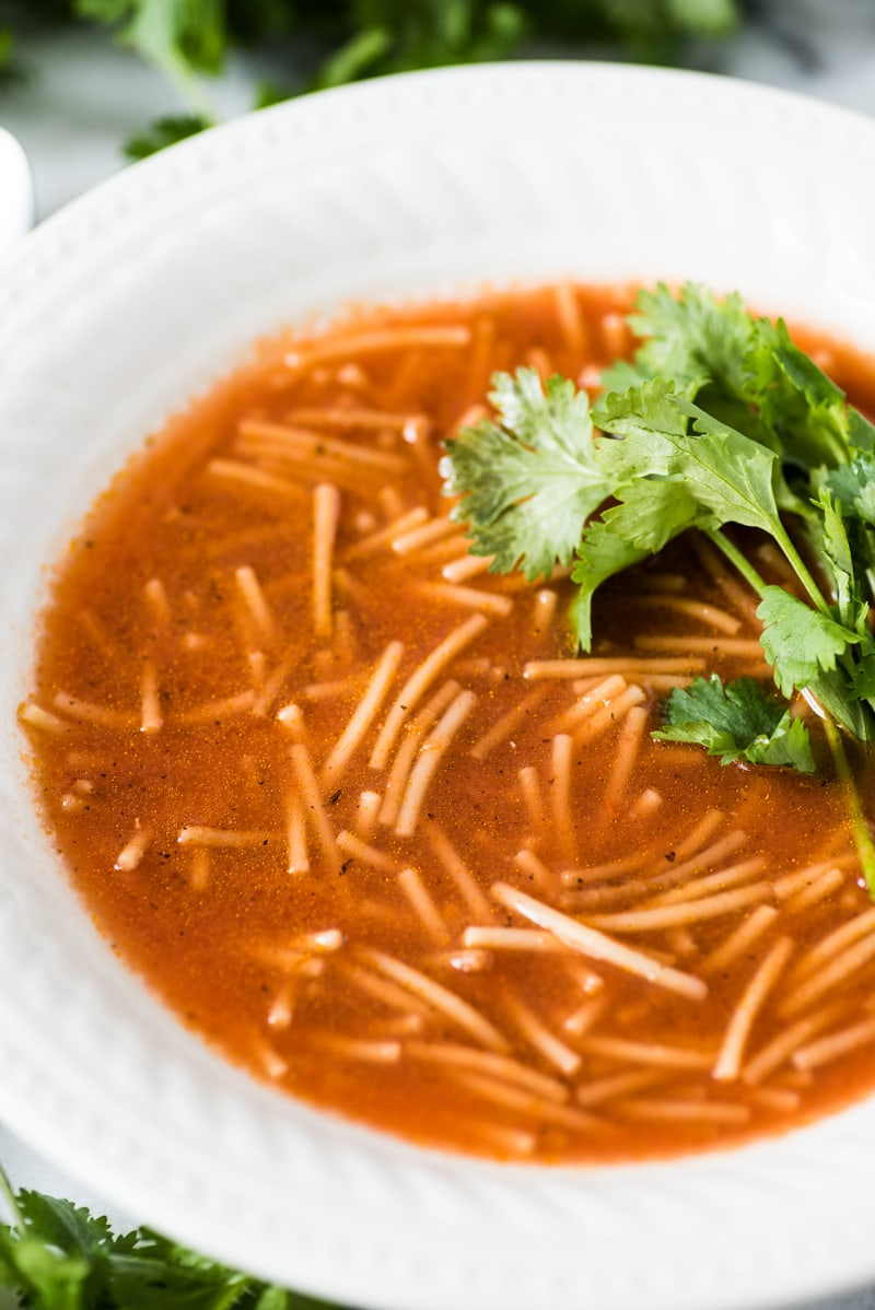 Sopa de fideo in a white bowl topped with cilantro.