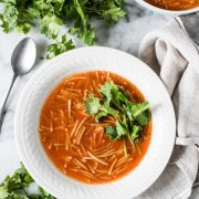 A white bowl filled with sopa de fideo (also known as mexican noodle soup) topped with cilantro.