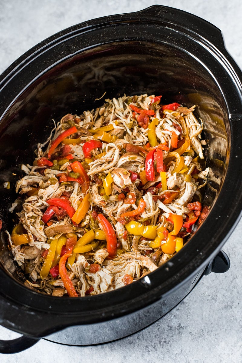 Chicken fajitas made with shredded chicken and fajita bell peppers in a large crockpot.
