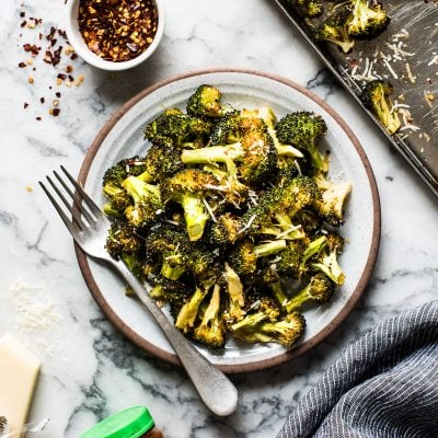 Ready in only 15 minutes, this Roasted Broccoli is tossed in a chili garlic sauce and topped with Parmesan cheese for a healthy and delicious veggie side dish!