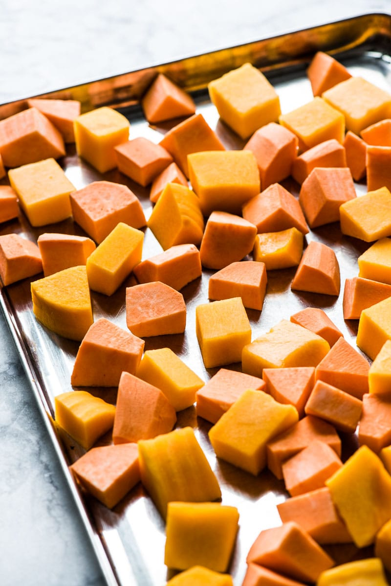 Cut sweet potatoes and butternut squash on a baking sheet to make healthy sweet potato casserole.