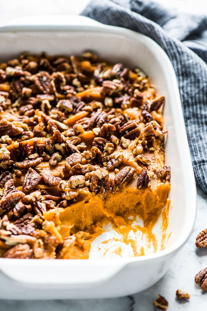 A healthy sweet potato casserole in a white baking dish topped with candied pecans.