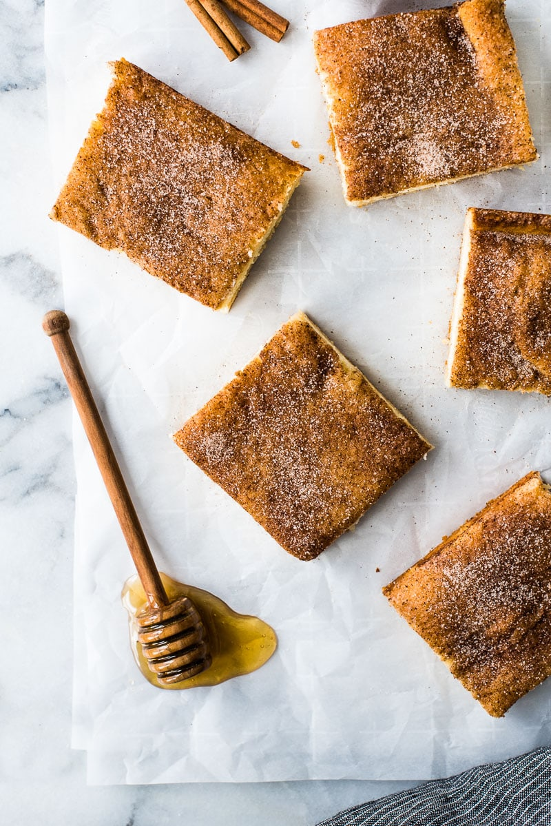 These Sopapilla Cheesecake bars are the perfect combination of light and airy crescent roll dough, creamy cheesecake filling and cinnamon sugar topping! Served with a side of honey.