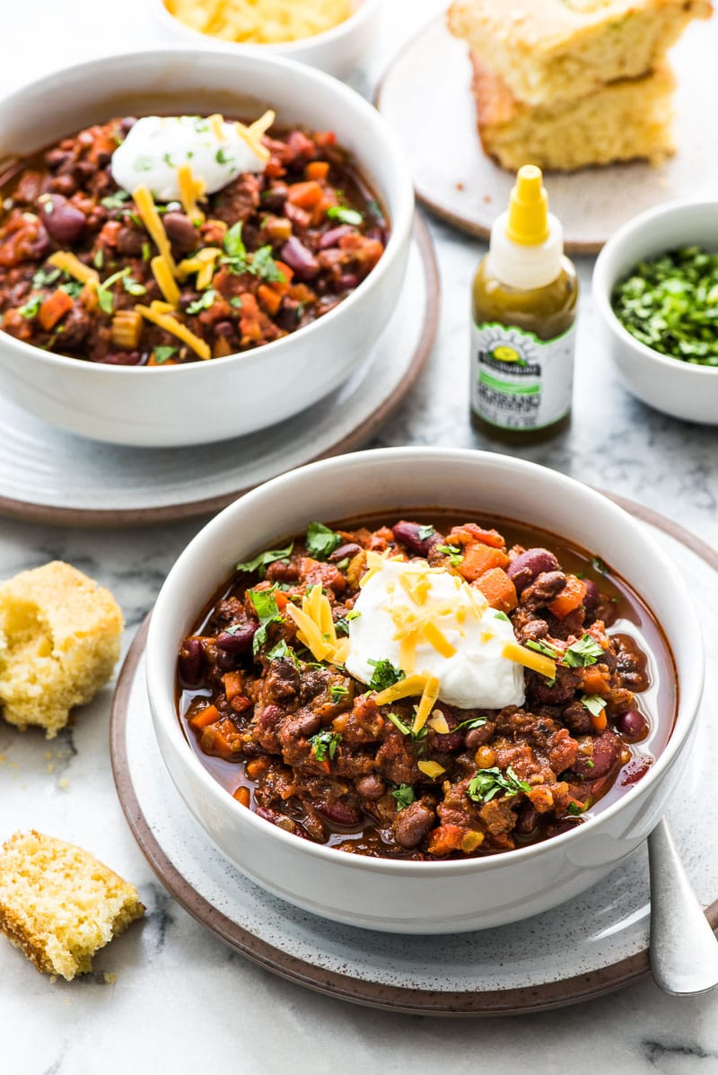 This Spicy Vegetarian Chili is thick, satisfying and super filling! Serve it with your favorite toppings for an easy and healthy meatless meal. (gluten free, vegetarian, vegan) Featuring Yellowbird hot sauce and served with jalapeno cornbread.