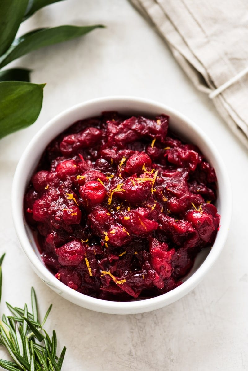 A cranberry sauce recipe in a white bowl topped with orange zest.