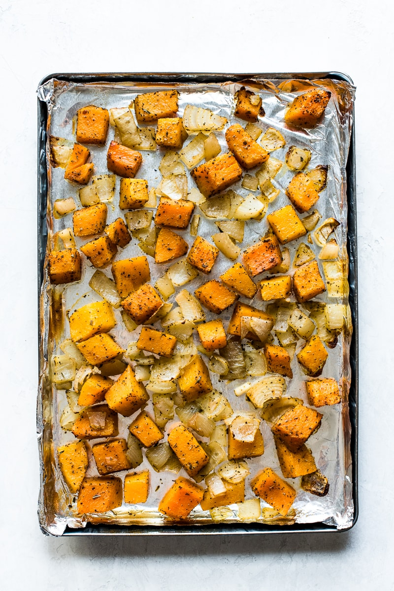 Roasted butternut squash and onions on a large baking sheet