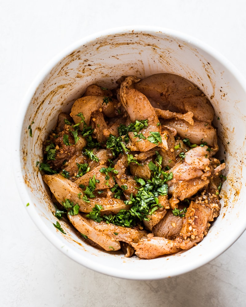 Sliced chicken breast in a white bowl in marinade made with cilantro.