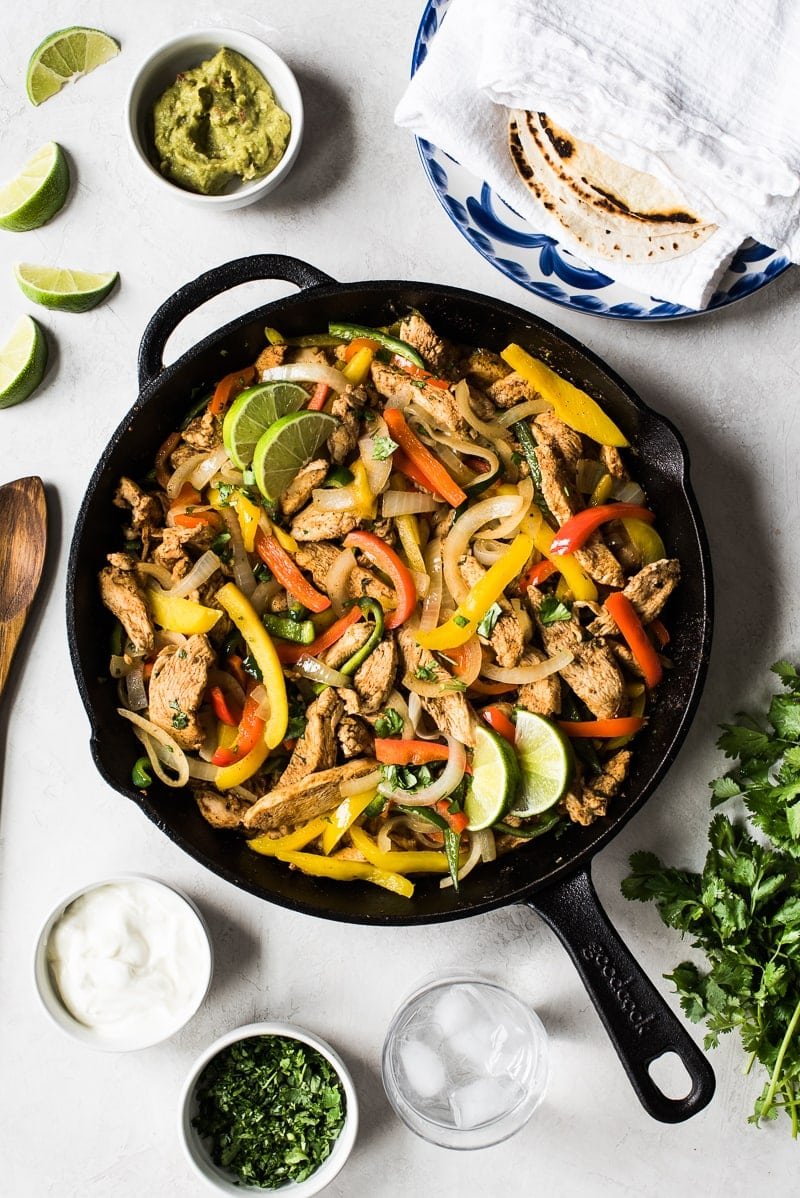 Chicken fajitas with peppers and onions in a black cast iron pan with Mexican ingredients around it.
