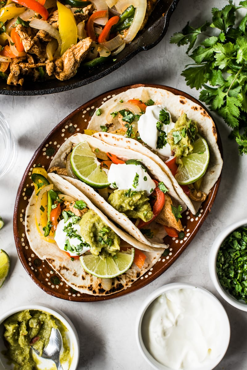 Chicken fajita tacos topped with sour cream, guacamole and chopped cilantro.