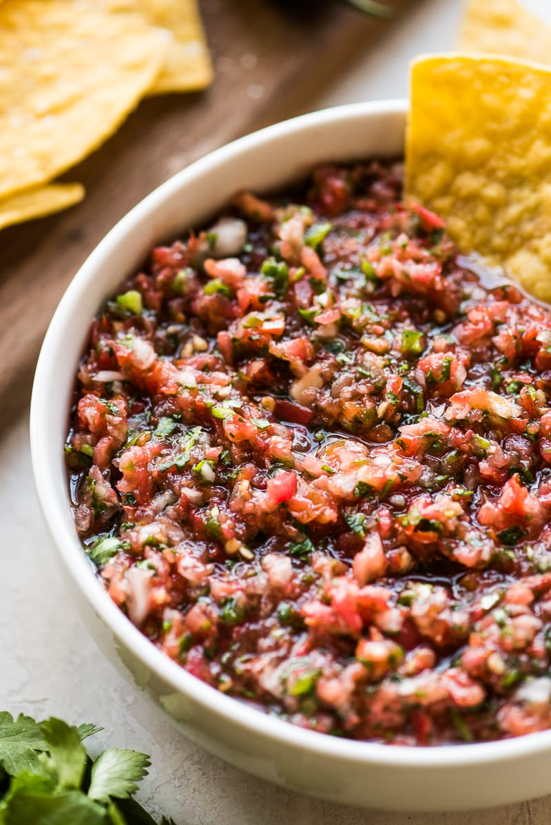 Homemade tomato salsa in a white bowl served with tortilla chips.