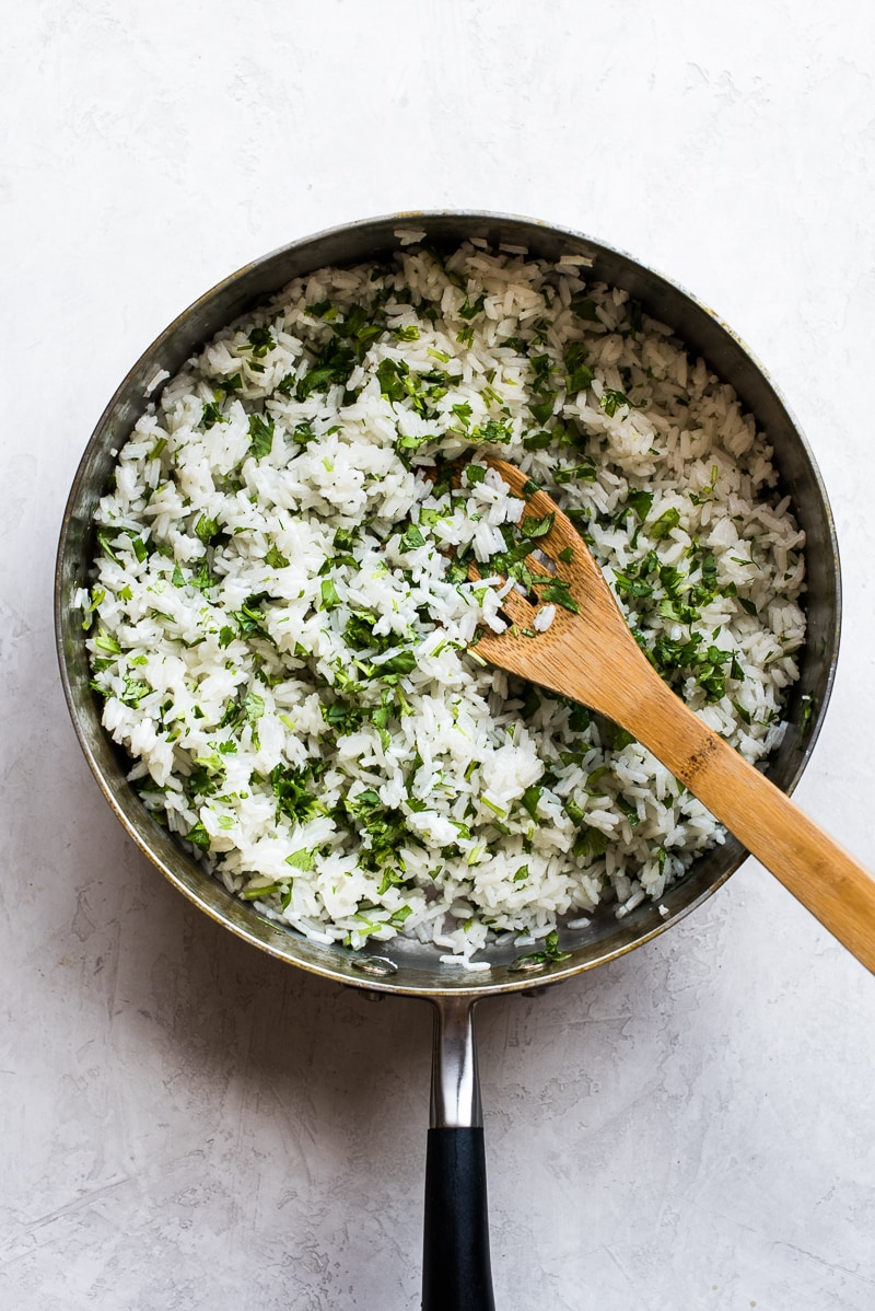 top down shot of cilantro lime rice in a pot with a wooden spoon