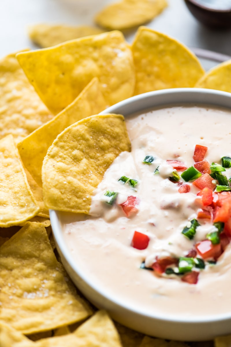 Mexican queso dip with a tortilla chip dipped in it.