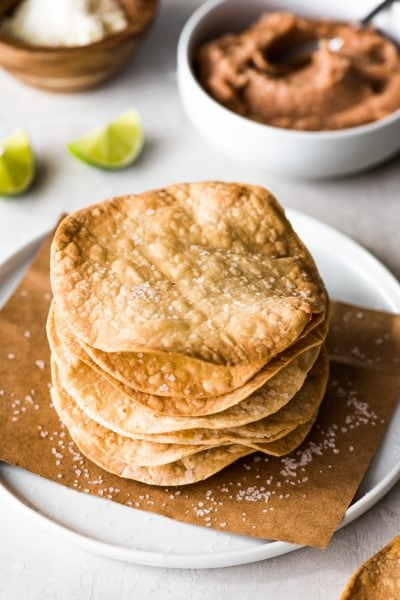 These Homemade Tostadas Shells are baked and ready in only 15 minutes! Top them with refried beans and cheese for a delicious Mexican weeknight meal.
