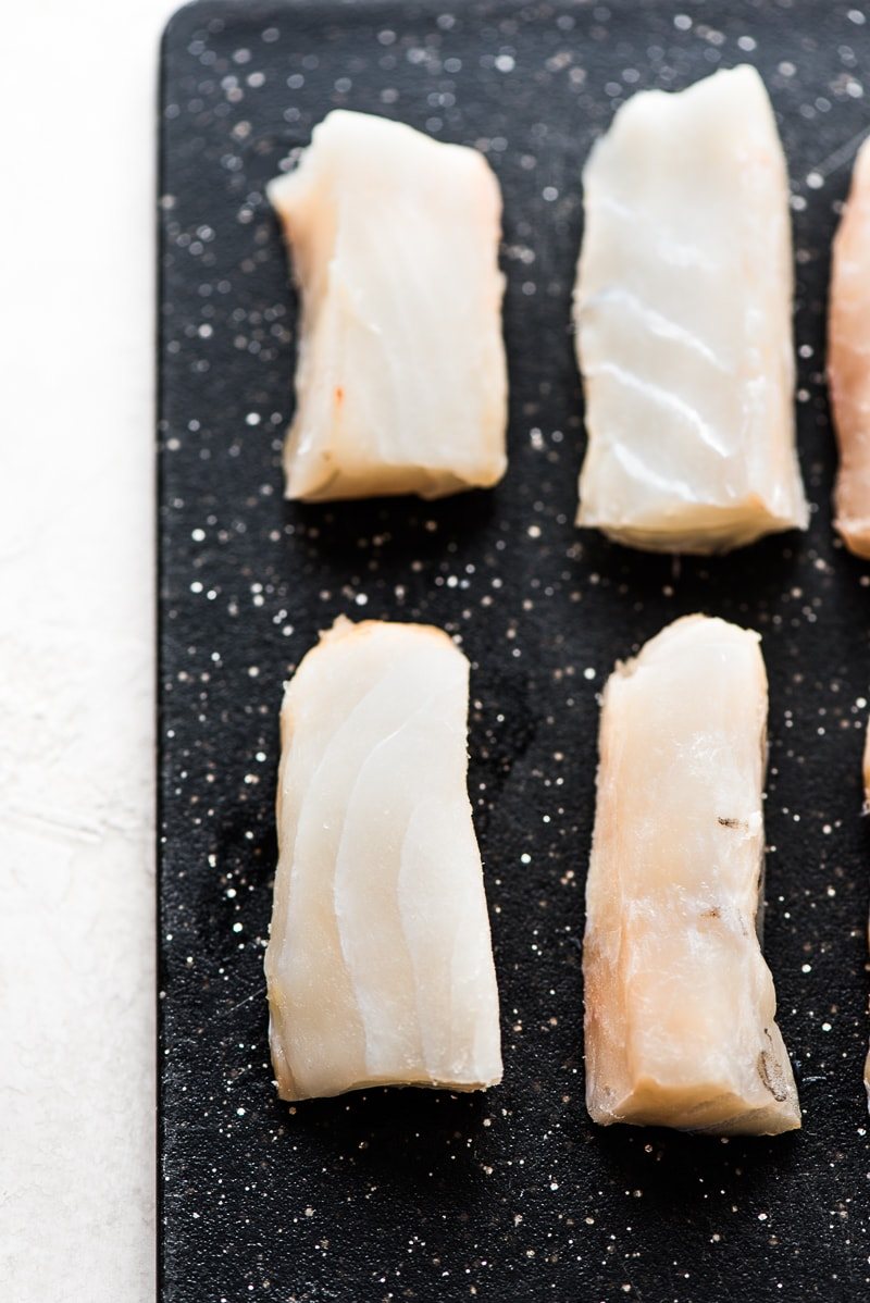 Sliced strips of Atlantic Cod on a black cutting board for Baja Fish Tacos recipe.