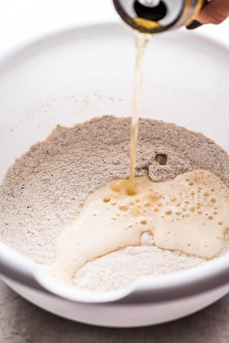 Beer being poured into a flour mixture for a Baja Fish Tacos recipe.