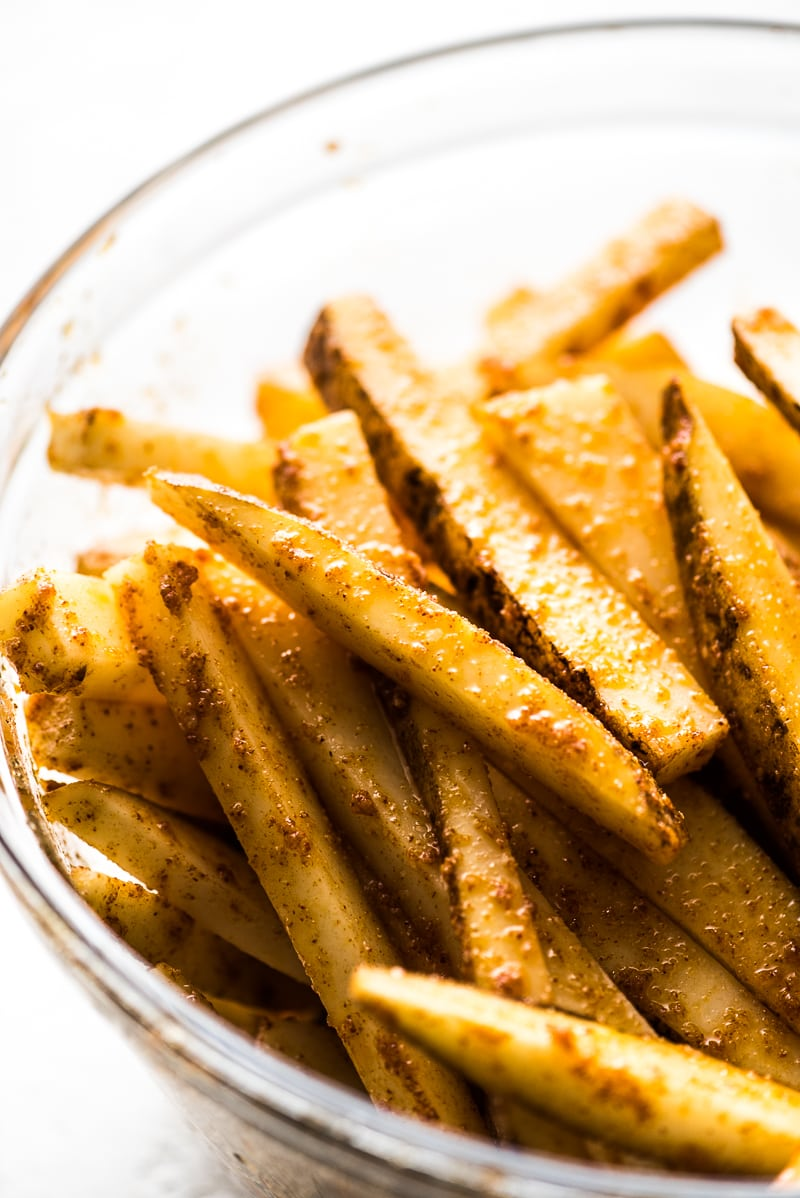 Fries in a mixing bowl seasoned with spices