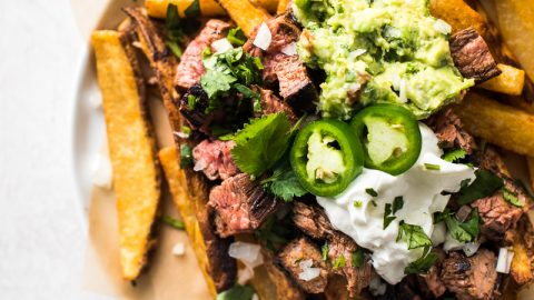 This Carne Asada Fries recipe is a San Diego classic featuring crispy baked fries topped with shredded cheese, tender carne asada, guacamole and sour cream!