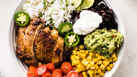 Chicken burrito bowl made with chicken, black beans, cilantro lime rice, corn, tomatoes, guacamole and sour cream.