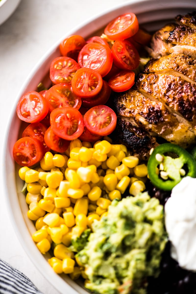 A copycat chipotle burrito bowl with chicken, tomatoes, corn and guacamole.