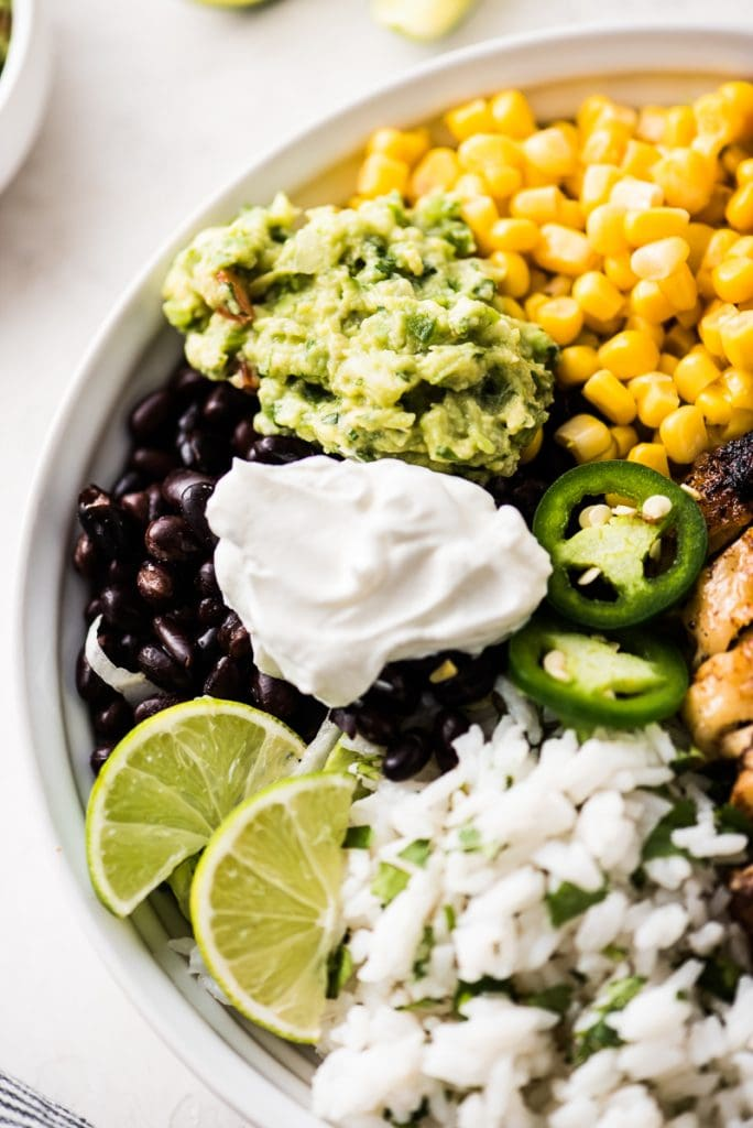 A chicken burrito bowl made with cilantro lime rice, black beans, corn, guacamole and plain Greek yogurt.