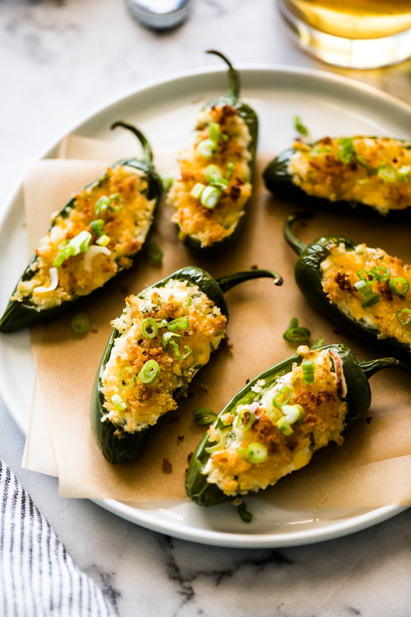 Baked Jalapeno Poppers stuffed with cream cheese and topped with panko breadcrumbs and green onions on a white plate.