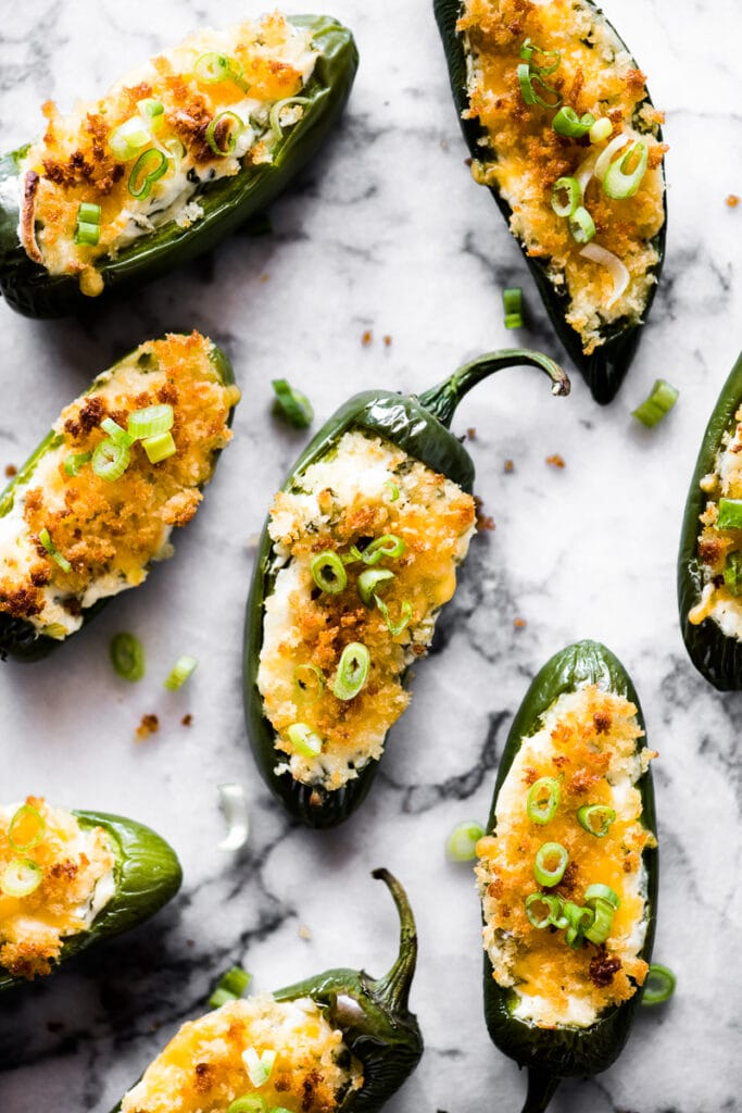 Overhead photo of baked jalapeno poppers topped with breadcrumbs and green onions on a marble countertop.