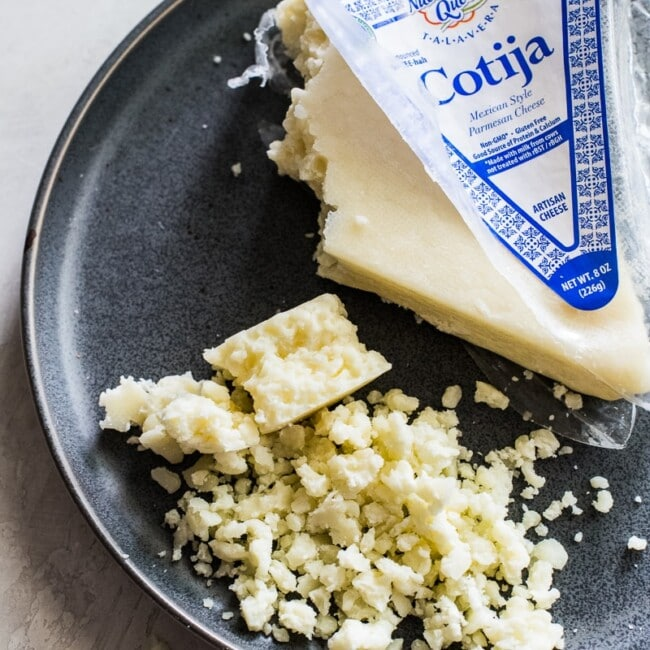 Crumbled cotija cheese on a gray stone plate.